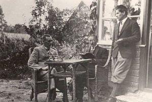 """Jakob Liiv oma aias uut käsikirja ette lugemas, vasakult Sarap, J. Liiv, Vihvelin. Foto: """"Odamees"""", 1929. RM F 55:1, SA Virumaa Muuseumid, http://www.muis.ee/museaalview/2104543."""