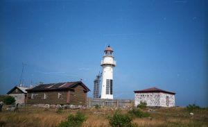 Mälestusmärgi avamine Vaindloo saarel Briti laevastiku meremeestele, kes hukkusid 1721. aastal. 1871. aastal ehitatud tuletorn (näha on päikesepatareid), vana õliladu paremal ja kuur vasakul. Taga paistmas kordonihoone nurk., MM F 1898/7, Eesti Meremuuseum SA, http://www.muis.ee/museaalview/2839024.