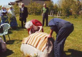 Foto: August Kondoja. Vinni-Tudu naisansambli toetusel kõlanud lipu laulu ajal eemaldasid kivilt katte küla põliselanik Helgi Pundi (Lepiku) ja Nelja tamme talu peremees Lembit Lehova.